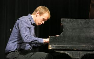 Music Clubhouse instructor Dan performs on piano on stage.