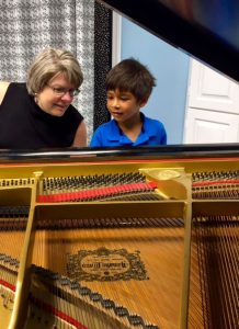 photo of Janet Hart Johnson at piano with a young boy during a piano lesson.