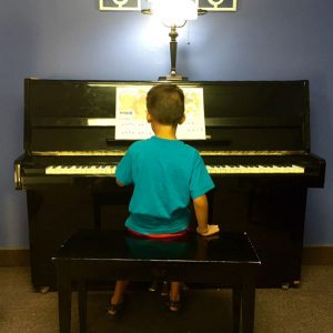 photo of a young boy sitting at the piano